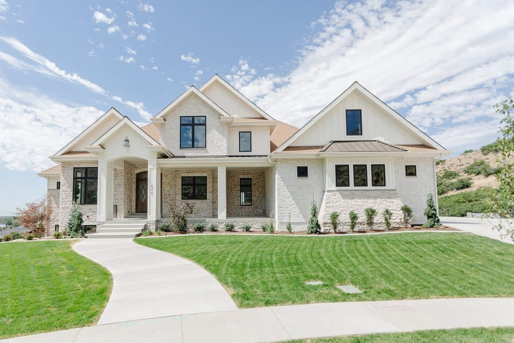 Highland Custom Homes Utah Valley Parade of Homes 2020 Front of Home showing natural stone & white brick in Full Sunlight.